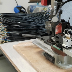 Naprava za kovičenje priključkov, v ozadju kabli s pokovičenimi priključki
