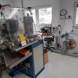 Delavnica (v ospredju naprava za razrez, posnemanje in kovičenje žic, v ozadju naprava za razrez in posnemanje kablov in odvijalec kablov)