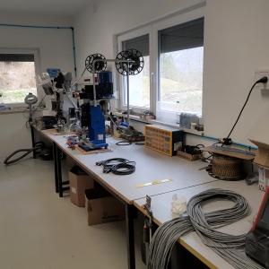 Delavnica (desno naprava za posnemanje kablov in žic, v sredini naprava za kovičenje, na levi druga naprava za kovičenje)